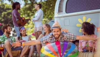 Happy hipsters having fun on campsite at a music festival