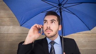 Serious businessman under umbrella phoning against wooden surface with planks