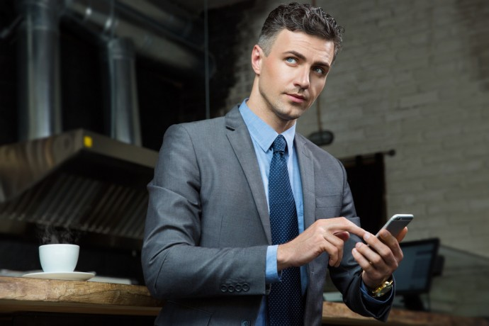 Handsome businessman holding smartphone and looking aside in cafe