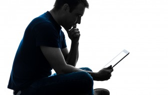 one  man sitting holding digital tablet in silhouette on white background