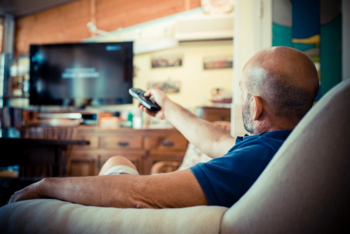miggle age man watching tv at home