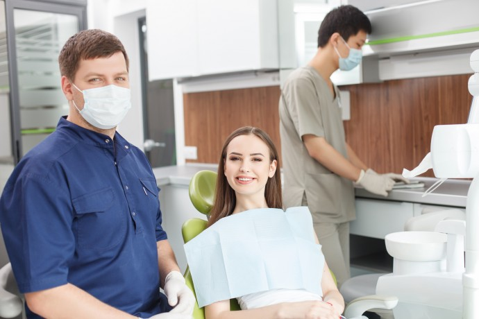 Cheerful young dentist is examining female teeth. He is looking at the camera happily. The woman is sitting in chair and smiling. The male assistant is working near them with concentration
