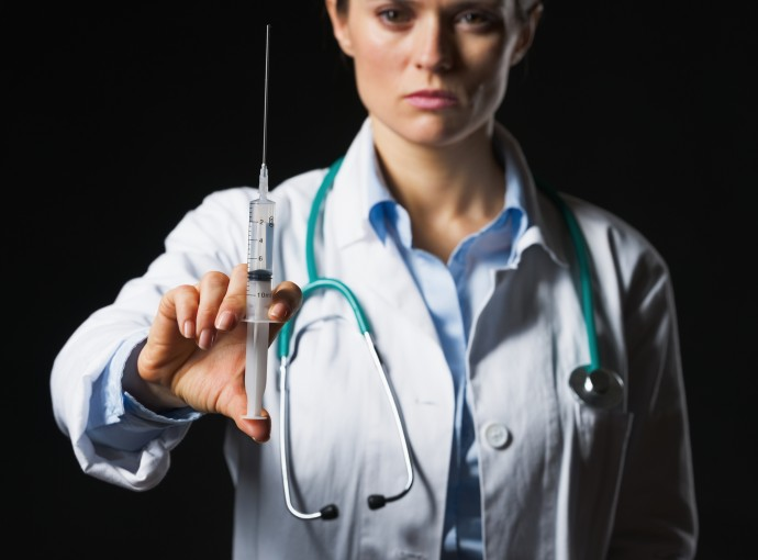 Closeup on syringe in hand of doctor woman isolated on black
