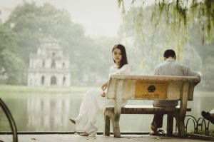 young-couple-sitting-on-bench-in-park-1