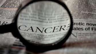 cancer-newspaper-word-magnifier-magnifying-glass