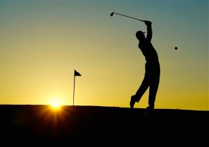 silhouette-of-man-playing-golf-at-sunset